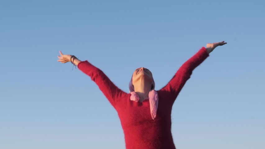 Cancer woman with open arms receives the sun and smiles for a new opportunity in a blue sky background