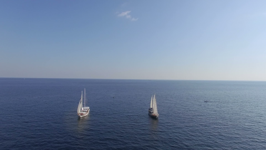 Two sailboats sail the sea bay. Aerial view of sailboats ride at sea bay. Ride on a sailboats boat at sea aerial   Shutterstock HD Video #1054451579