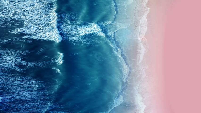 Aerial view of sea and sand beach at sunset. Pink sand beach with ocean wave foams. Beautiful top view of sunset pink sand beach. Perfect for holiday summer background, Tropical destination.  Royalty-Free Stock Footage #1054451963