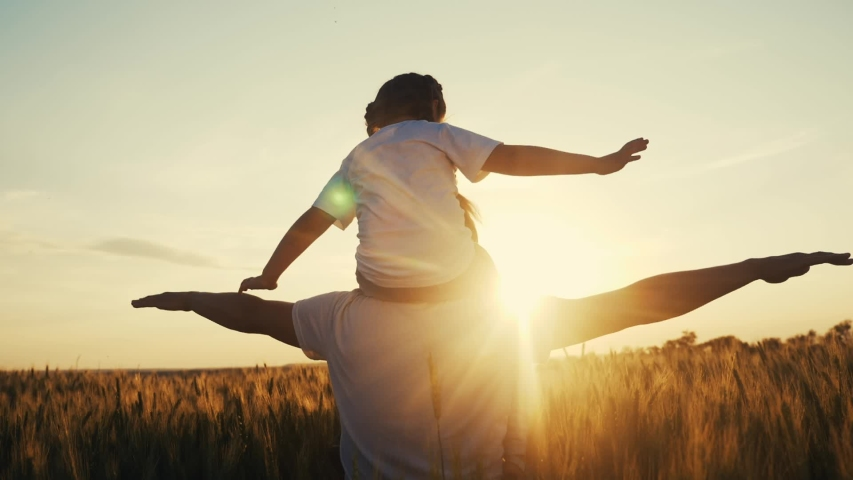 Father and daughter. daughter sits on the dad neck silhouette in a field in the park. happy family kid dream concept. father and daughter playing pilot hands to the sides dreaming shows airplane fun Royalty-Free Stock Footage #1054453124