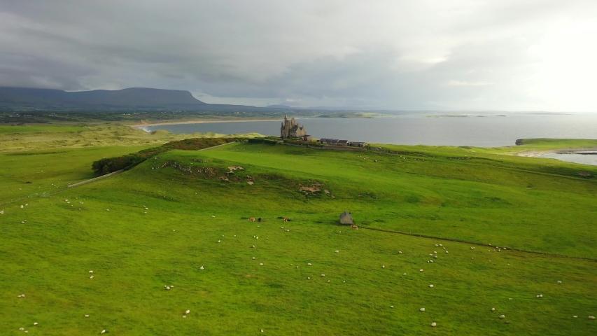Classiebawn Castle in green rural landscape in Ireland, distant backwards aerial | Shutterstock HD Video #1054459610