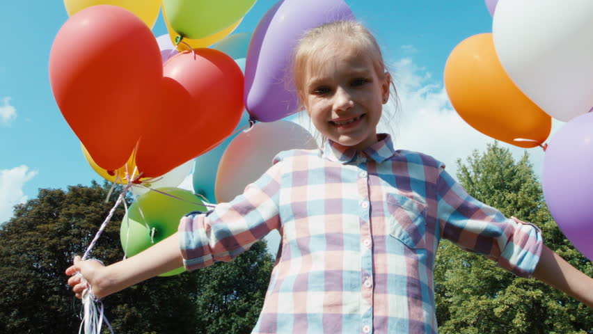 Closeup portrait happy girl spinning with balloons against the sky | Shutterstock HD Video #10544630