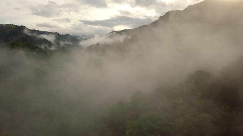 Aerial view flying thru the morning rain cloud covered tropical rain forest mountain landscape during the rainy season on the Doi Phuka Mountain reserved national park the northern Thailand