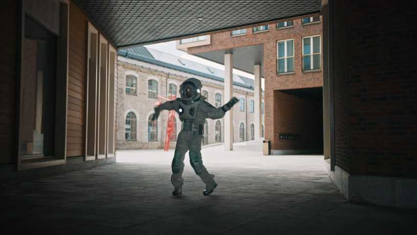 Handsome Man in Spacesuit is Dancing in a Neighbourhood. Astronaut is Happy and Makes Creative Robotic Moves. Successful Spaceman in White Futuristic Suit with Technological Panel on His Hand.