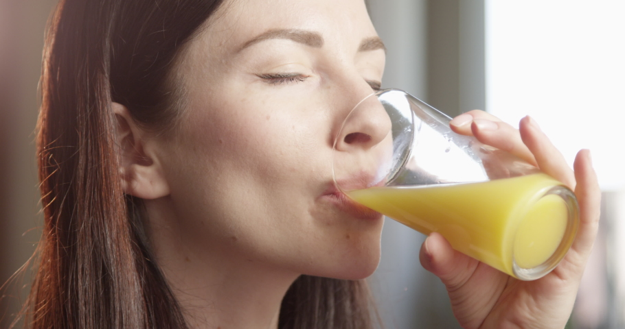Thirsty Woman Drinking Orange Juice Indoors with Sun Shining a Close up Shot on Red Camera