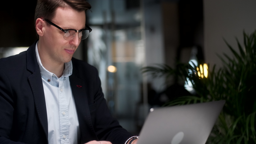 Young Business Man Sitting at His Desk at Home or Office, Typing on Laptop Doing Research And Smile. Busy Worker Freelancer Working on Modern Tech Notebook Device. Royalty-Free Stock Footage #1054466972