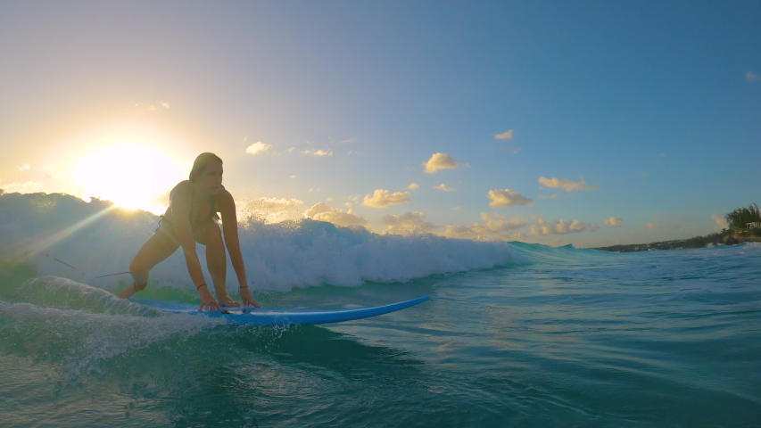 SLOW MOTION, LENS FLARE: Cinematic shot of a female beginner surfer riding a small wave to the tropical coast at sunset. Woman learning to surf stands up on her longboard and rides a wave at sunrise.
