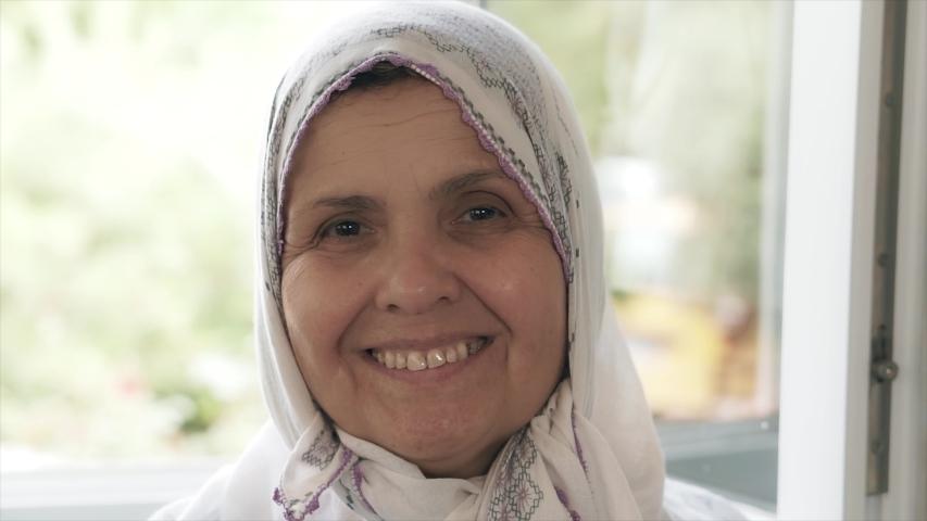 An old Muslim woman portrait. Cheerful hijab Islamic Turkish mother is smiling.  | Shutterstock HD Video #1054475453