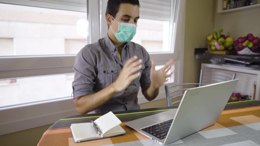 boy making a video conference with face mask  Royalty-Free Stock Footage #1054476614