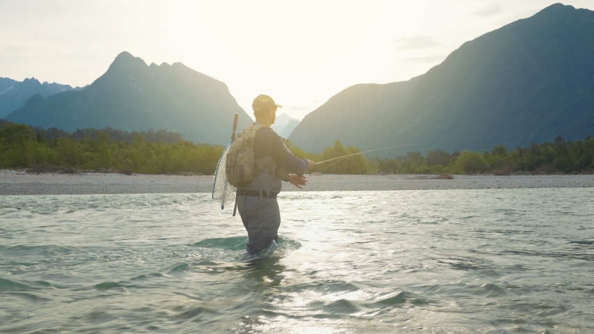A fully equipped fisherman swinging the fishing line to cast salmon on a sunny morning Royalty-Free Stock Footage #1054477613