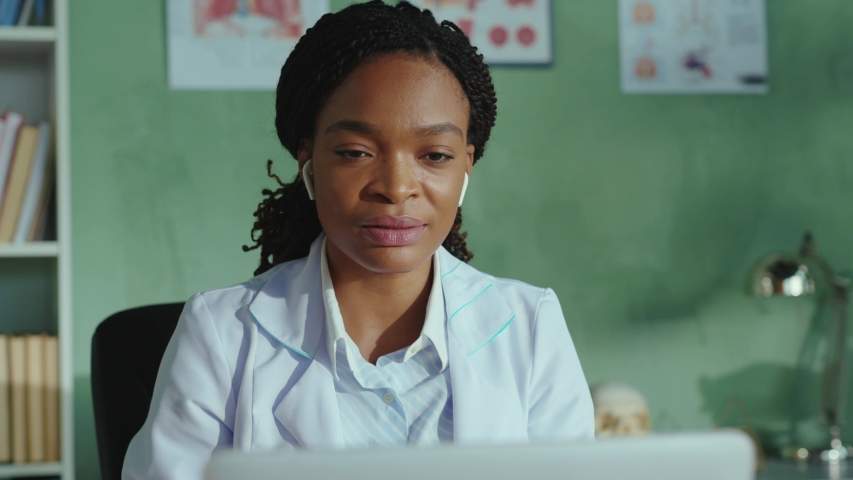 Afro-american friendly female doctor talking on laptop webcam explaining diagnosis remotely to distant client via online videochat telemedicine consultation. Hospitals. Medical staff.