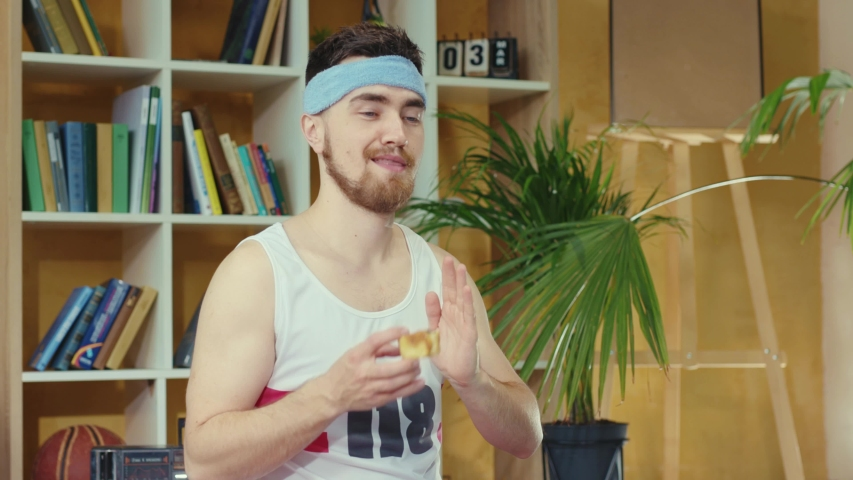 Caucasian funny retro guy pretends to meditate, practicing relaxing yoga asana, secretly taking and eating cookie. Junk food. Silly jerk. Concept of fun, humor, joke and sports. | Shutterstock HD Video #1054477979