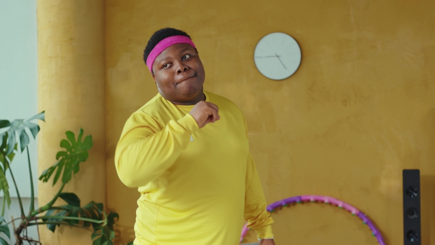 Fat handsome retro style young man dancing into music, doing warm-up exercises aerobics session training at home. Workout. Sports beginner. Funny activity.
