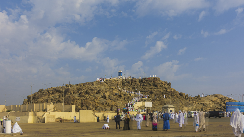 Time lapse of Muslims at Mount Arafat (or Jabal Rahmah) in Arafat, Saudi Arabia. This is the place where Adam and Eve met after being overthrown from heaven. Zoom out motion timelapse. Prores UHD