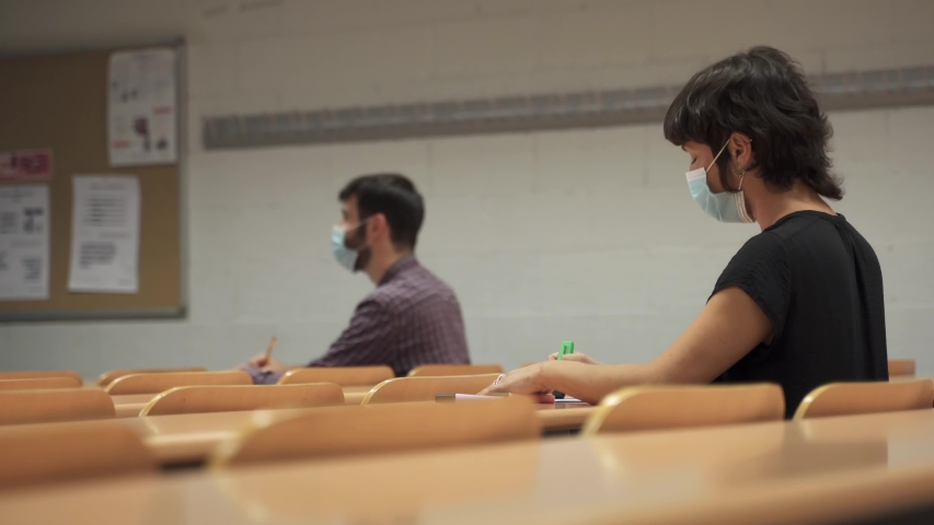 University students with face masks sitting in empty classroom due to Coronavirus Pandemic Measures in Education | Shutterstock HD Video #1054480847