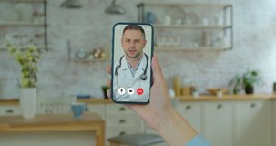 Beautiful woman checks possible symptoms with professional physician, using online video chat. Young girl sick at home using smartphone to talk to her doctor via video conference medical app.