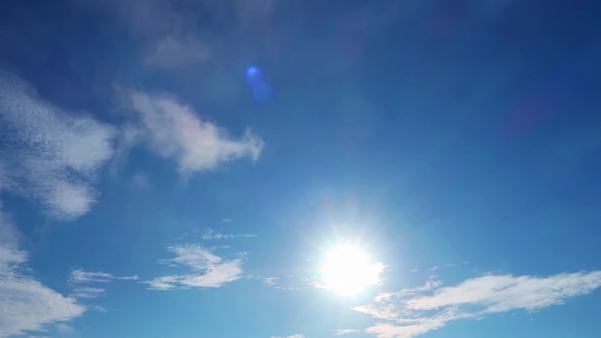 TimeLapse of Bright sun light, sunbeams & flares shining through sunrise clouds & cloudscape on beautiful sunny blue sky background in tropical summer sunlight ray at sunshine day, solar energy vdo   Royalty-Free Stock Footage #1054484309