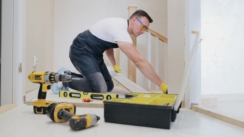 Carpenter worker installing laminate flooring in the corridor near the stairs. Joiner installs the last laminated board. Lots of instruments on the foreground   Shutterstock HD Video #1054491248