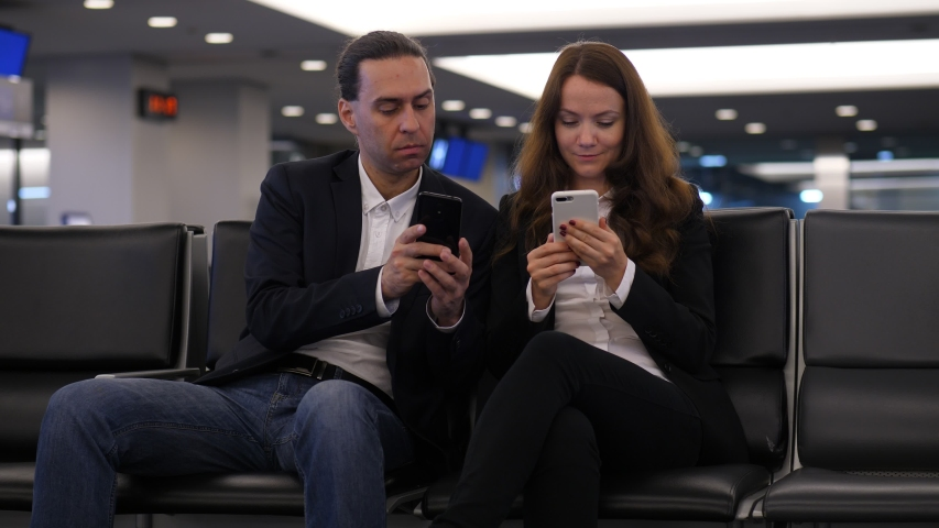 Man and woman sit with phones at airport lounge, passengers waste time before flight. Guy show something on smartphone, woman shift closer and look to screen