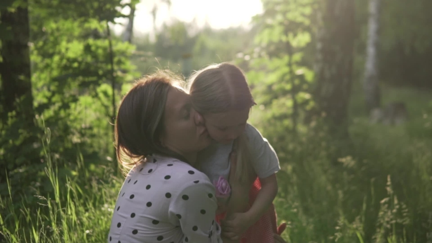 Gentle mom and daughter on a walk through the summer park at sunset. Baby gives her mother a flower, a woman gently kisses the child