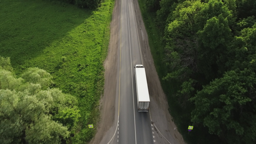One Semi Truck with white trailer and cab driving / traveling alone on dense flat forest asphalt straight road, highway top view follow vehicle aerial footage / Freeway trucks traffic Royalty-Free Stock Footage #1054495421