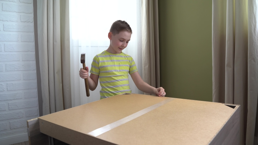 4K. a fair-Haired freckled teenager collects and repairs wooden furniture in the room, hammering iron nails with a hammer. | Shutterstock HD Video #1054496711