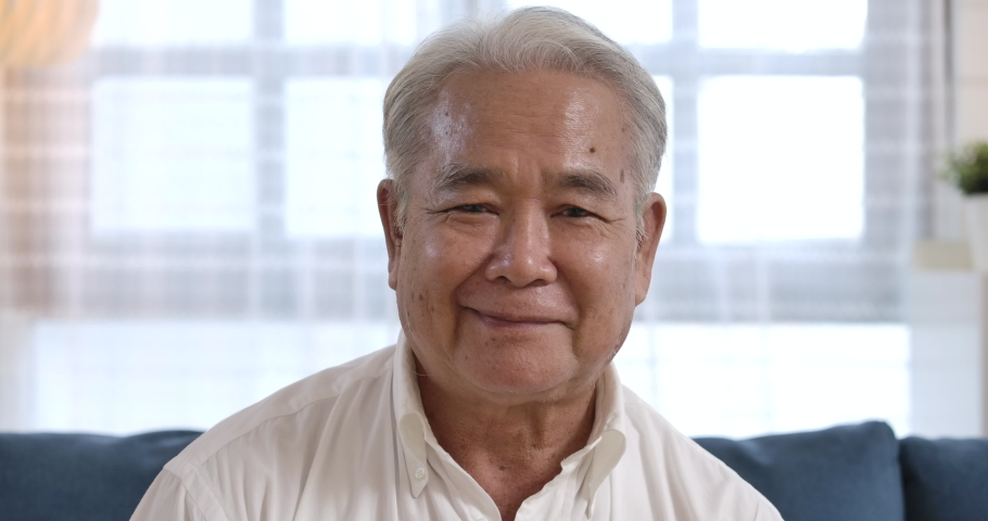 Closeup face portrait of healthy cheerful asian senior elderly old gray-haired man smiling to the camera while sitting on the blue couch in the living room. happy mature middle aged grandfather.
