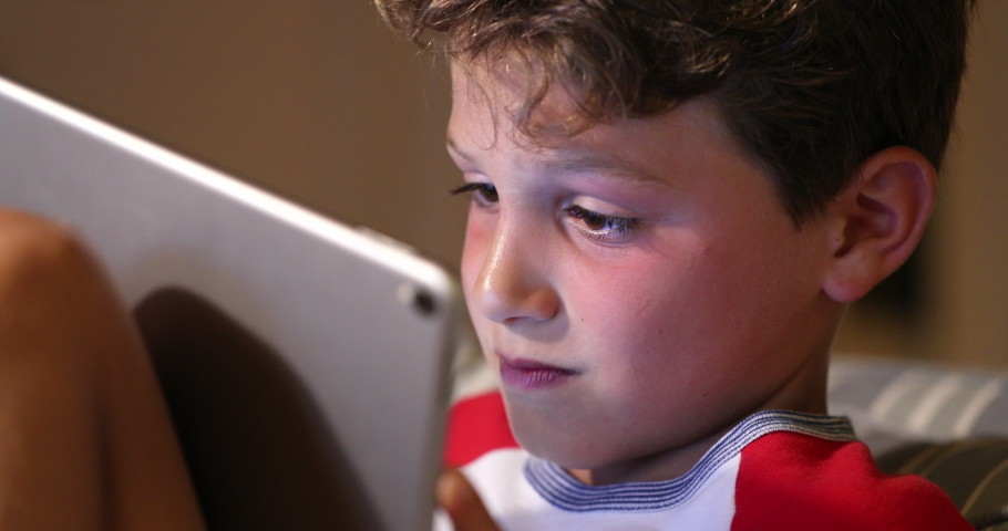 Child addicted to video-game playing online with tablet tech. Bboy holding device absorbed by game