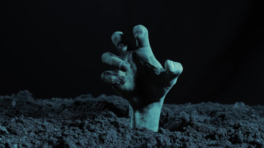Zombie hand rising out from the grave