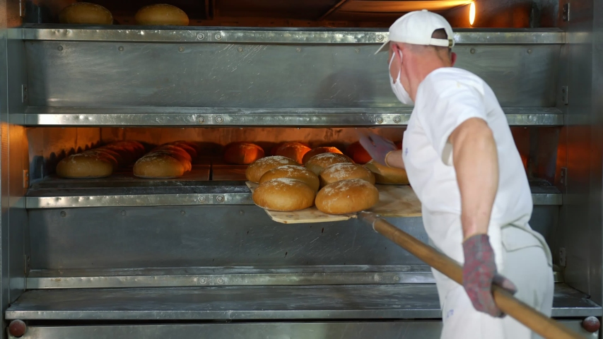Chef removes freshly baked bakery products from the oven. Baked bread is removed from the oven in a bakery. | Shutterstock HD Video #1054502213