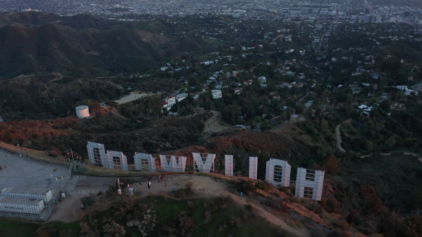 AERIAL: Breathtaking Tilt up over Hollywood Sign Letter from back revealing Los Angeles Cityscape in Beautiful Sunset Light  | Shutterstock HD Video #1054506803