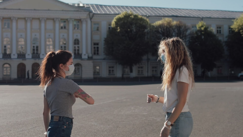 two girls Friends in protective masks meet on the street they bump elbows Royalty-Free Stock Footage #1054508909