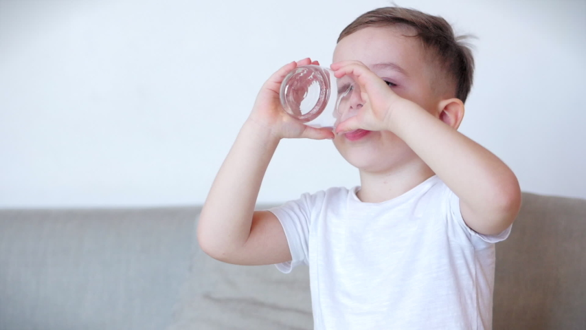 Cute baby boy drinking a glass of water sitting on the couch at home. Slow motion little boy drinking water. Close-up. Portrait Funny little Child is drinking a cup of water.