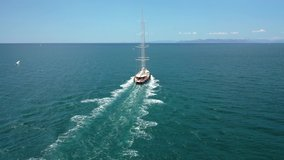 Aerial drone video of beautiful wooden deck classic sailing yacht cruising in open ocean deep blue sea