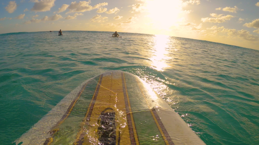 POV, LENS FLARE: Sitting in line up on a vintage longboard, observing the golden sunset during a fun surfing trip in the Caribbean. Surfer sits on surfboard and waits for waves on a sunny evening.