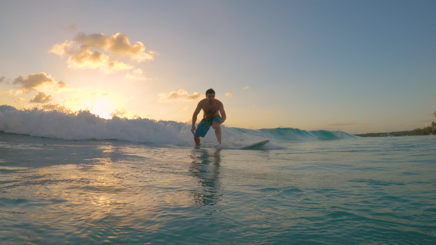 SLOW MOTION, LOW ANGLE: Cinematic shot of a happy male surfer riding a small wave to the tropical coast. Cheerful surfer dude on vacation in Barbados rides a small wave on a picturesque summer evening