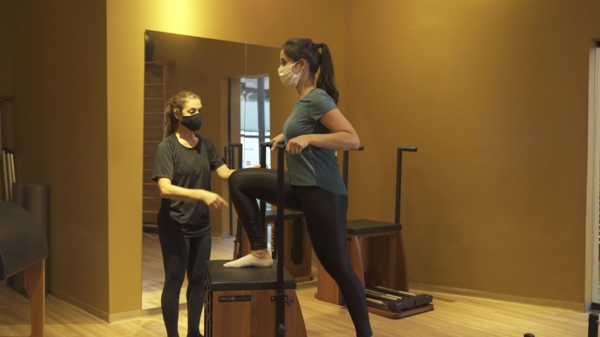 Pilates. Classes with a trainer wearing face mask agains corona virus at the gym Pilates on a special simulator. Loosen restrictions. Reopen    Shutterstock HD Video #1054510973