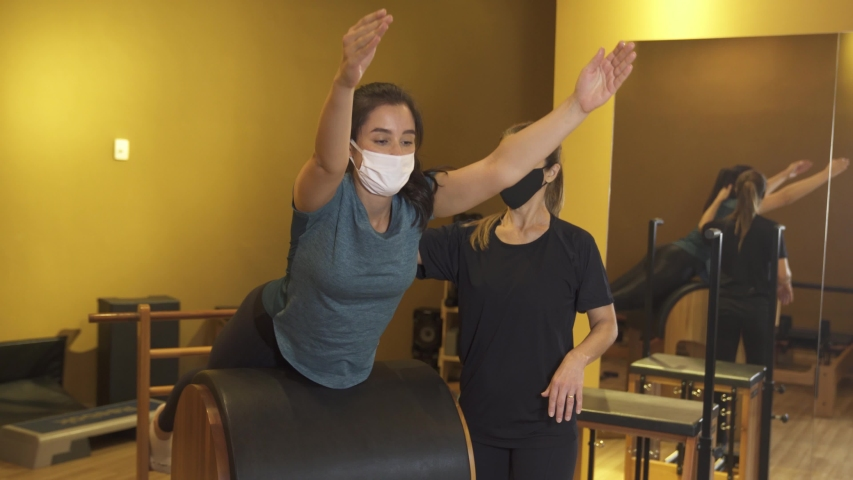 Pilates. Classes with a trainer wearing face mask agains corona virus at the gym Pilates on a special simulator. Loosen restrictions. Reopen   Shutterstock HD Video #1054510976