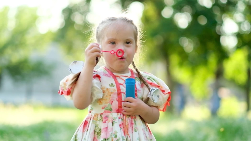 A girl with Down syndrome blows bubbles. The daily life of a child with disabilities. Chromosomal genetic disorder in a child. Royalty-Free Stock Footage #1054511483