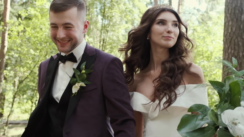 newlyweds hold hands in the forest.nice couple of lovers.slow motion wedding video Royalty-Free Stock Footage #1054511642
