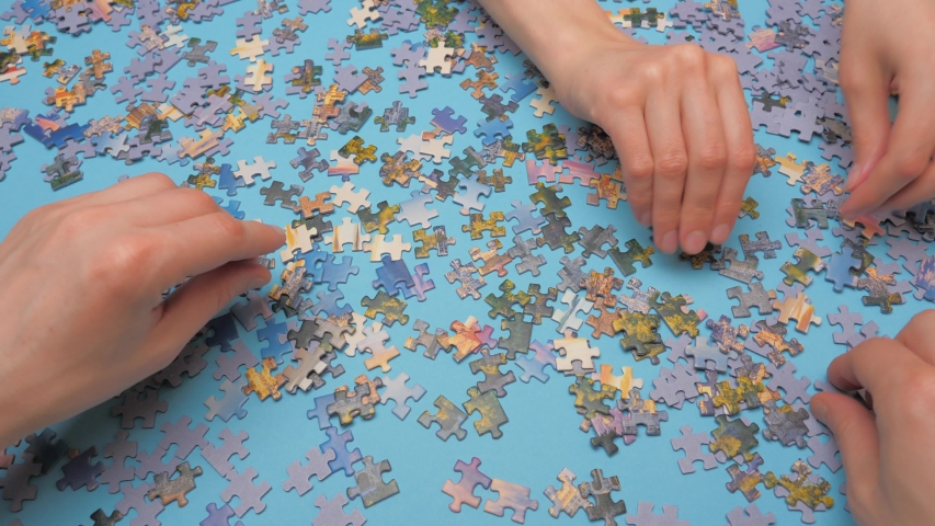 Placing pieces of puzzle face up. Family leisure time. Four hands assembling puzzle. Oddly shaped interlocking and mosaiced pieces of jigsaw. Fully interlocking puzzle. Jigsaw puzzle enthusiasts