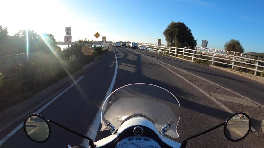 A motorbike rides over a bridge in a coastal town POV | Shutterstock HD Video #1054514264
