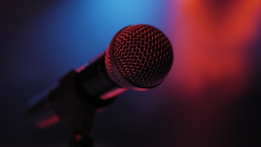 Concert microphone on the stage in the dark with the light red and blue bright lights. Microphone in a smoke on a dark background. Music instrument concept.