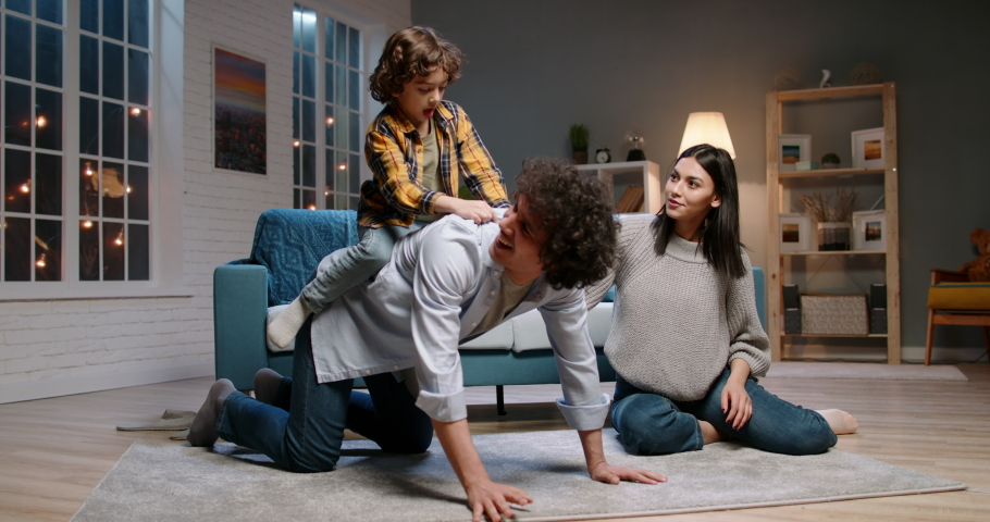 Funny asian family relaxing at home together. Little kid with curly hair jumping onto his father, doing a piggy back ride and laughing - happy family, recreational pursuit 4k footage | Shutterstock HD Video #1054518461