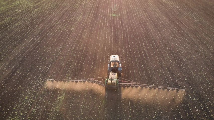 Aerial view of farming tractor spraying on field with sprayer, herbicides and pesticides at sunset. Farm machinery spraying insecticide to the green field, agricultural natural seasonal spring works. Royalty-Free Stock Footage #1054519223