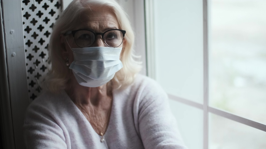 Elderly 73 year old woman with gray hair wearing a protective mask looking at the city from their hospital window. epidemic localization. | Shutterstock HD Video #1054519841