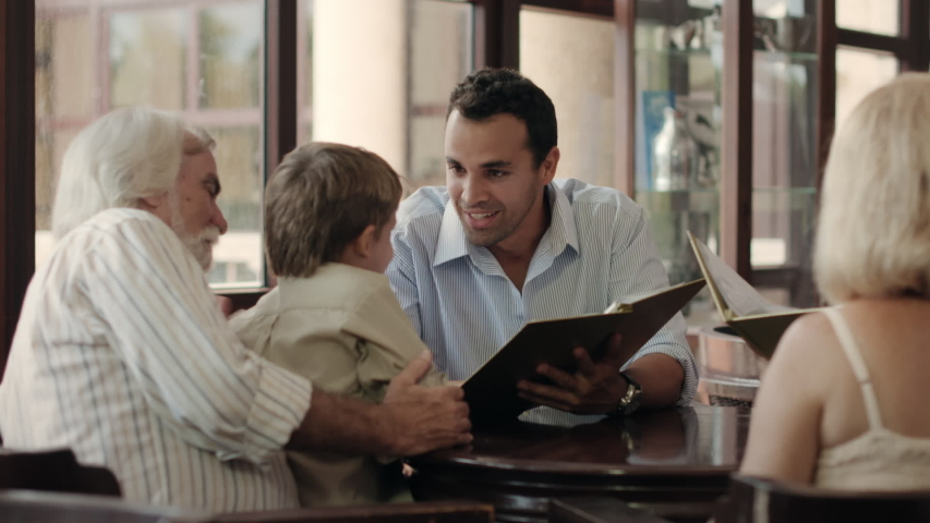 Happy family with father, mother, son, grandfather and grandmother choosing food and drinks in bar. Leisure and lifestyle with parents, grandparents and boy at restaurant. Dolly shot Royalty-Free Stock Footage #1054527860