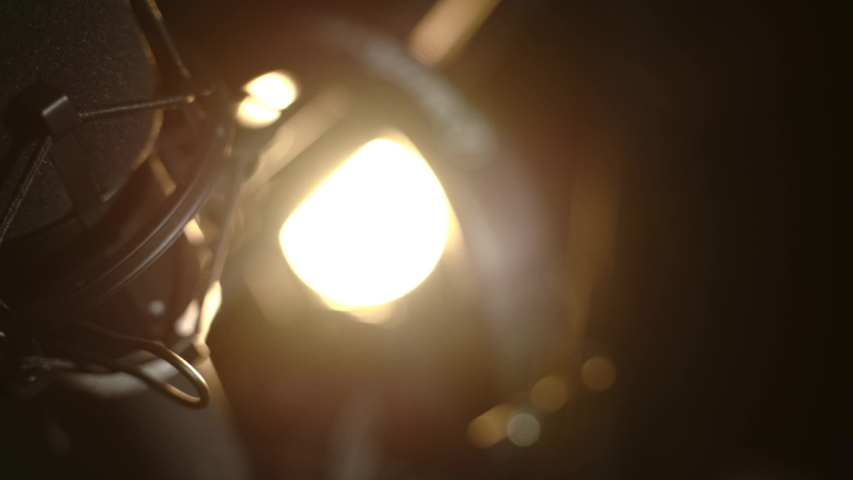 Slow pan of a podcast mic with backlighting for cinematic flare Royalty-Free Stock Footage #1054531322