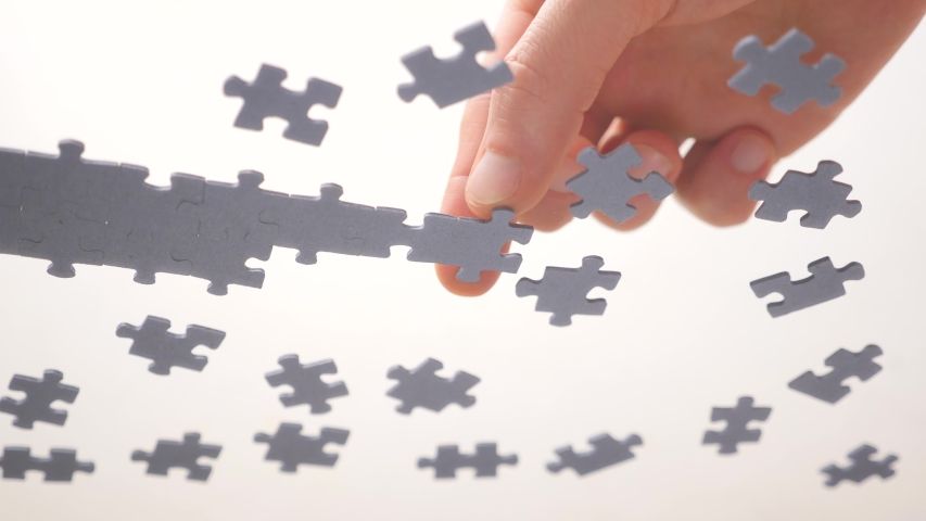 Assembling jigsaw puzzle. Pieces of a jigsaw puzzle interconnecting by male hand. Fast learning concept. Finding solution for business. Part of the whole. Assigning to learn a segment Royalty-Free Stock Footage #1054537493