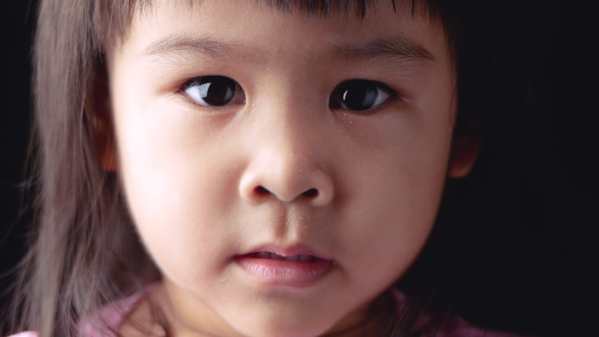 Portrait face of Asian little child girl with show your determination on dark background.
